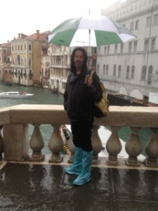 Wet in Venice. Our intrepid correspondent not taking risks. A hood as well as a brolly!